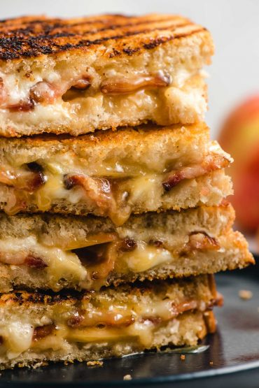 Stack of Brie Grilled Cheese that shows the gooey cheese and bacon on the inside.