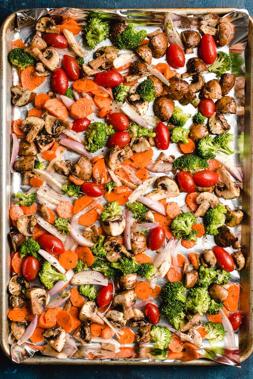 Sheet pan full of raw vegetables including shallots, broccoli, carrots, tomatoes, and mushrooms.