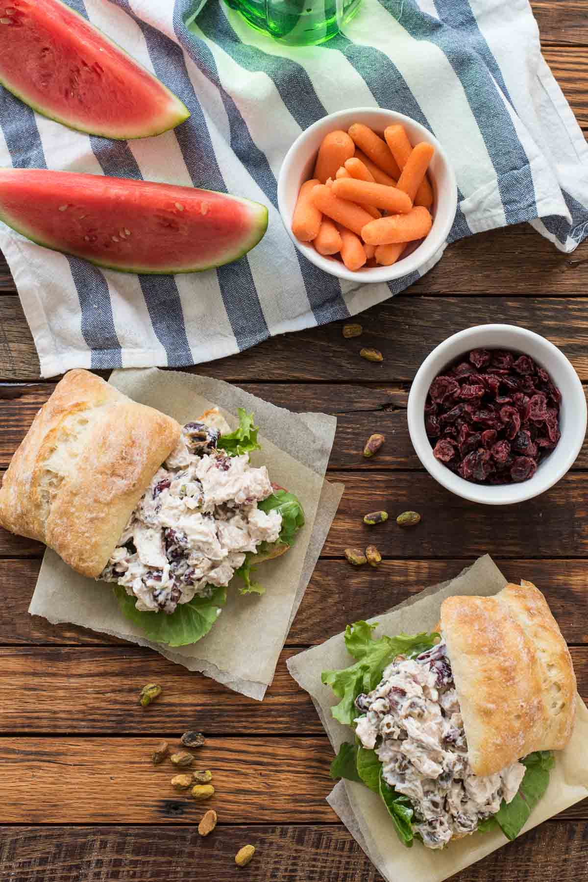 Picnic table with Cranberry Chicken Salad Sandwiches, watermelon slices, and carrots