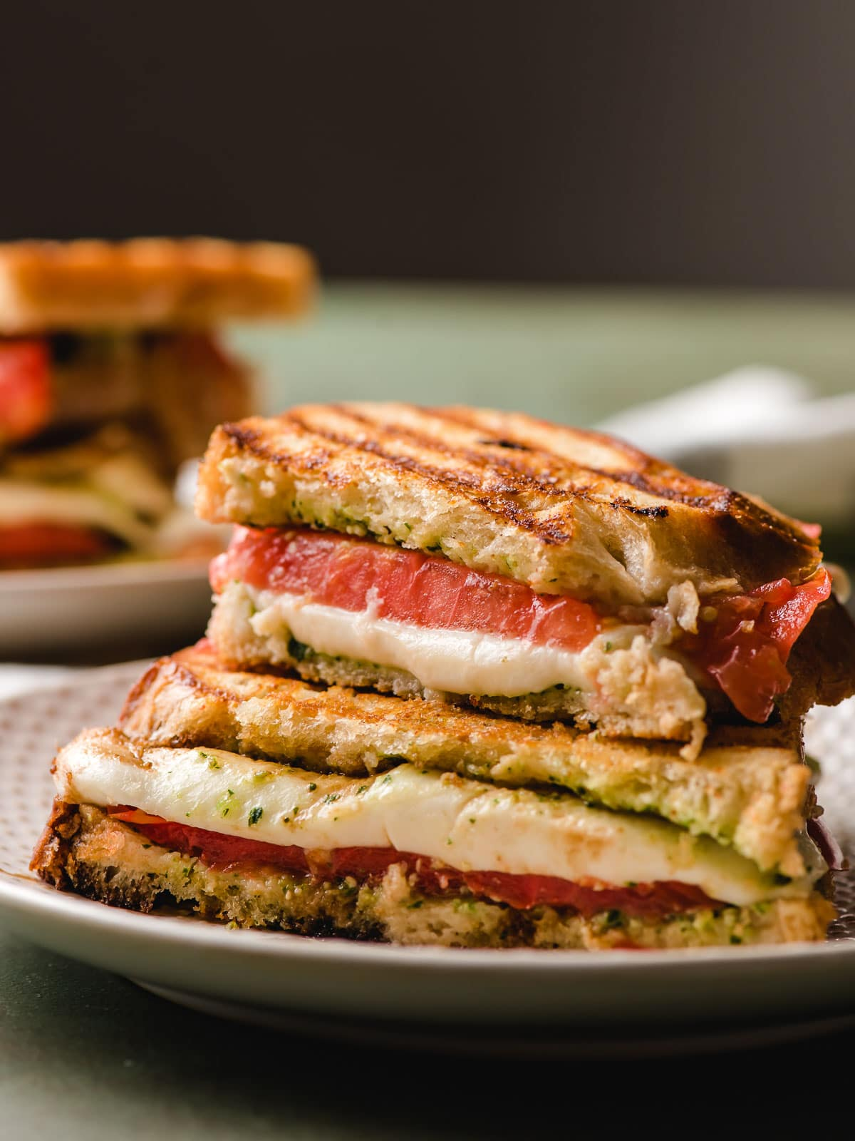 A halved Caprese Grilled Cheese shown with mozzarella melting out the center.