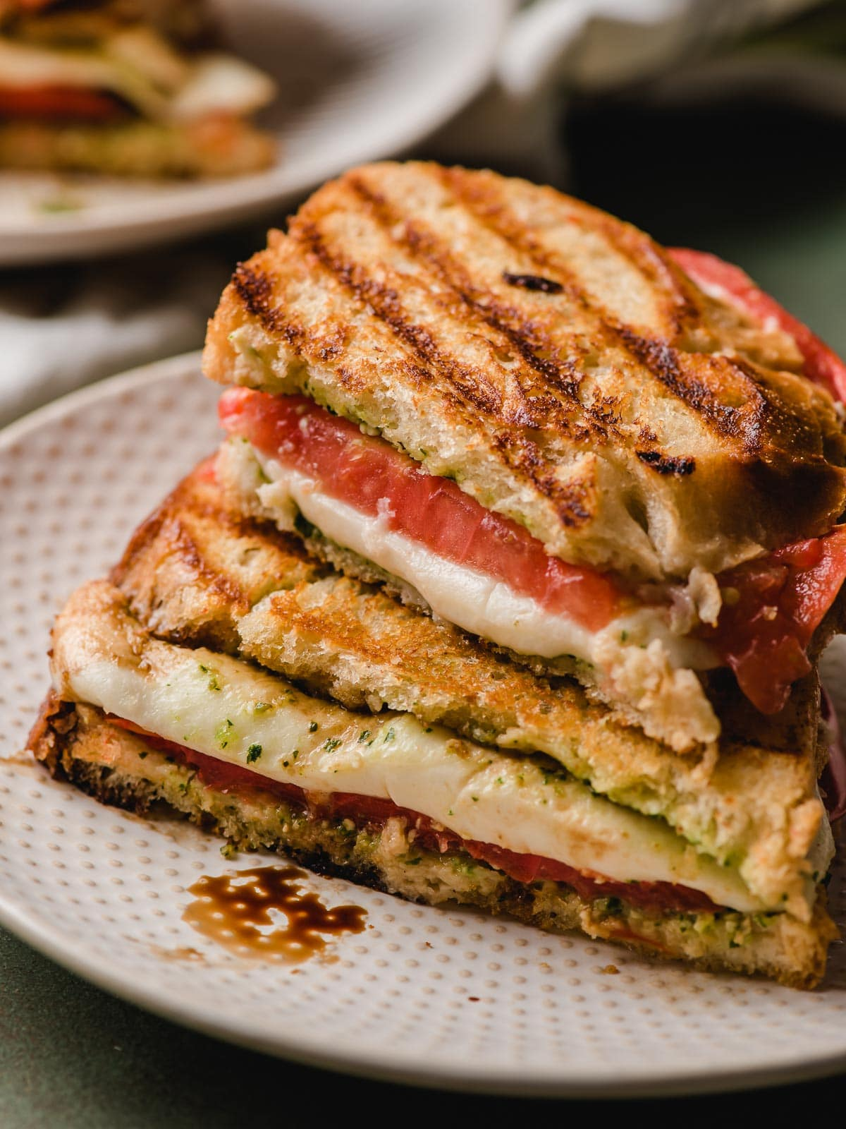 A grilled Caprese panini shown stacked on a white decorative plate.