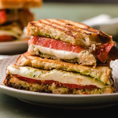 Caprese Panini halved and stacked on a white plate, with mozzarella melting down the front.