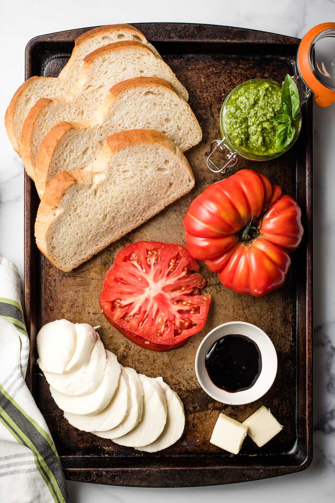 Sandwich ingredients on a baking sheet- sliced tomato, mozzarella, butter, pesto, bread, and balsamic vinegar.