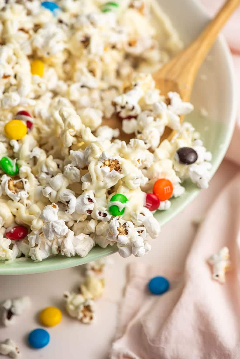 scoop of white chocolate popcorn and M&MS