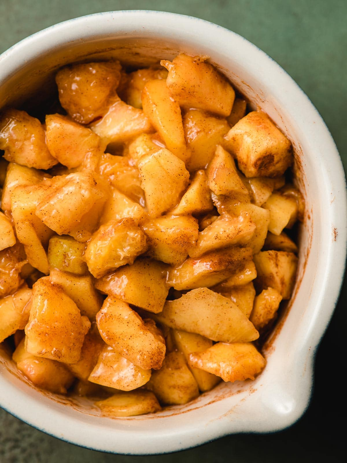 Bowl of fresh diced peaches with cinnamon.