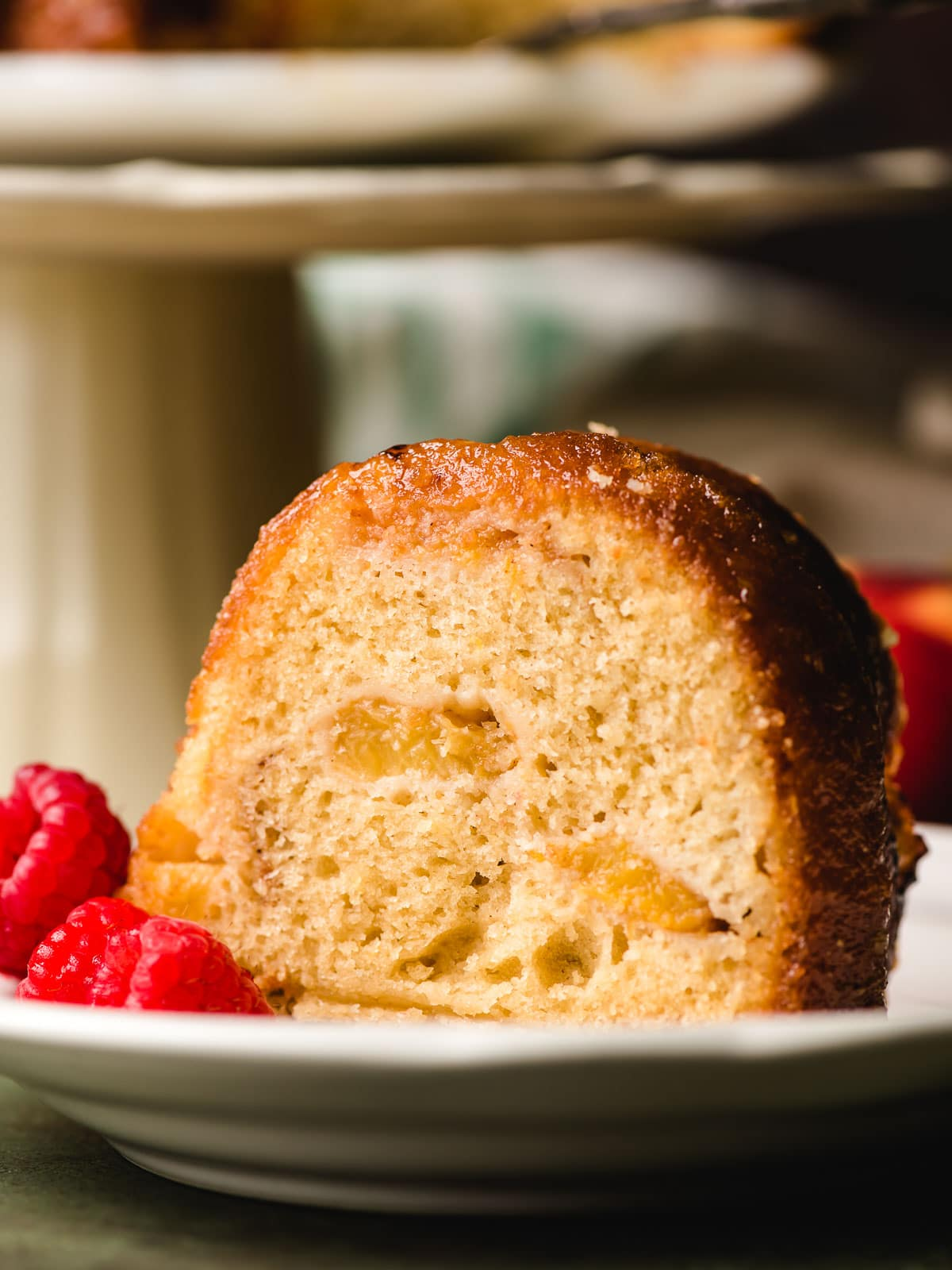 Sliced of peach bundt cake on a white plate with raspberries.