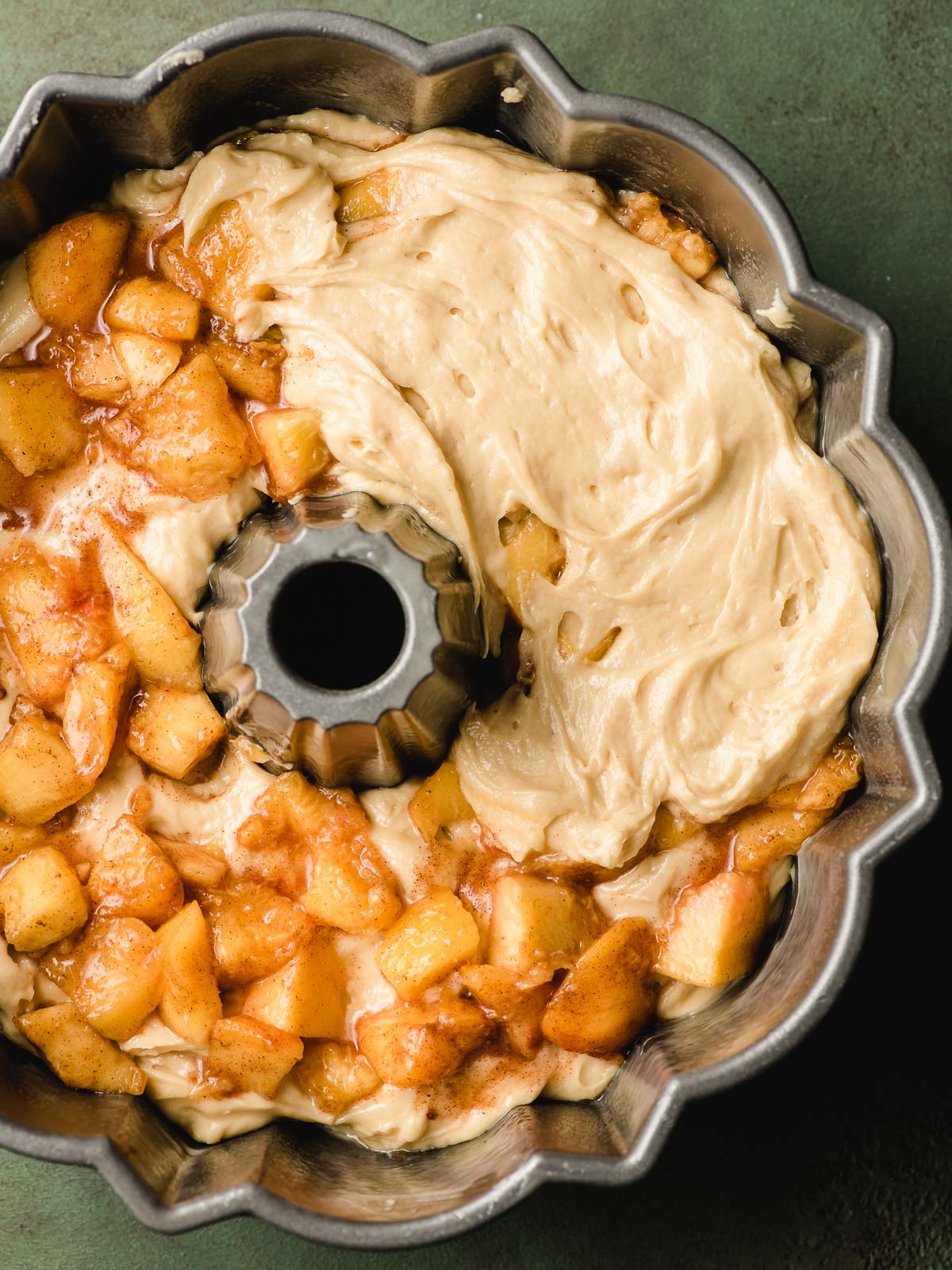 Diced peaches and cake batter layered in a bundt pan.