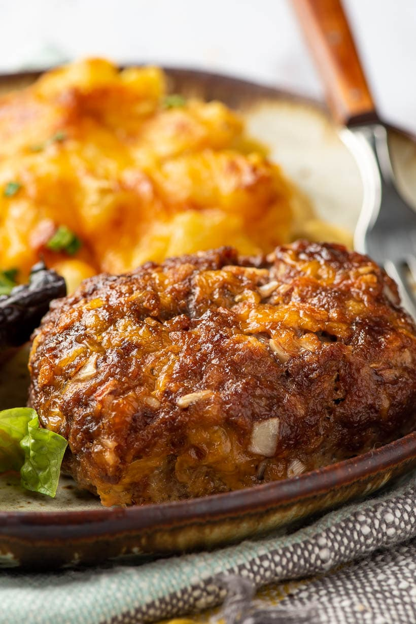 cheesy meatloaf on a brown rimmed plate