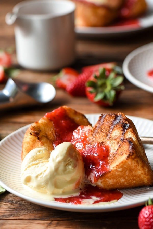 Grilled Angel Food Cake with ice cream and strawberry rhubarb sauce on a plate