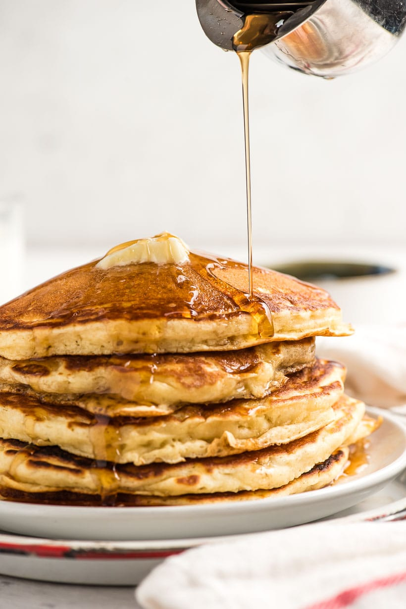stack of fluffy buttermilk pancakes with syrup being poured on top