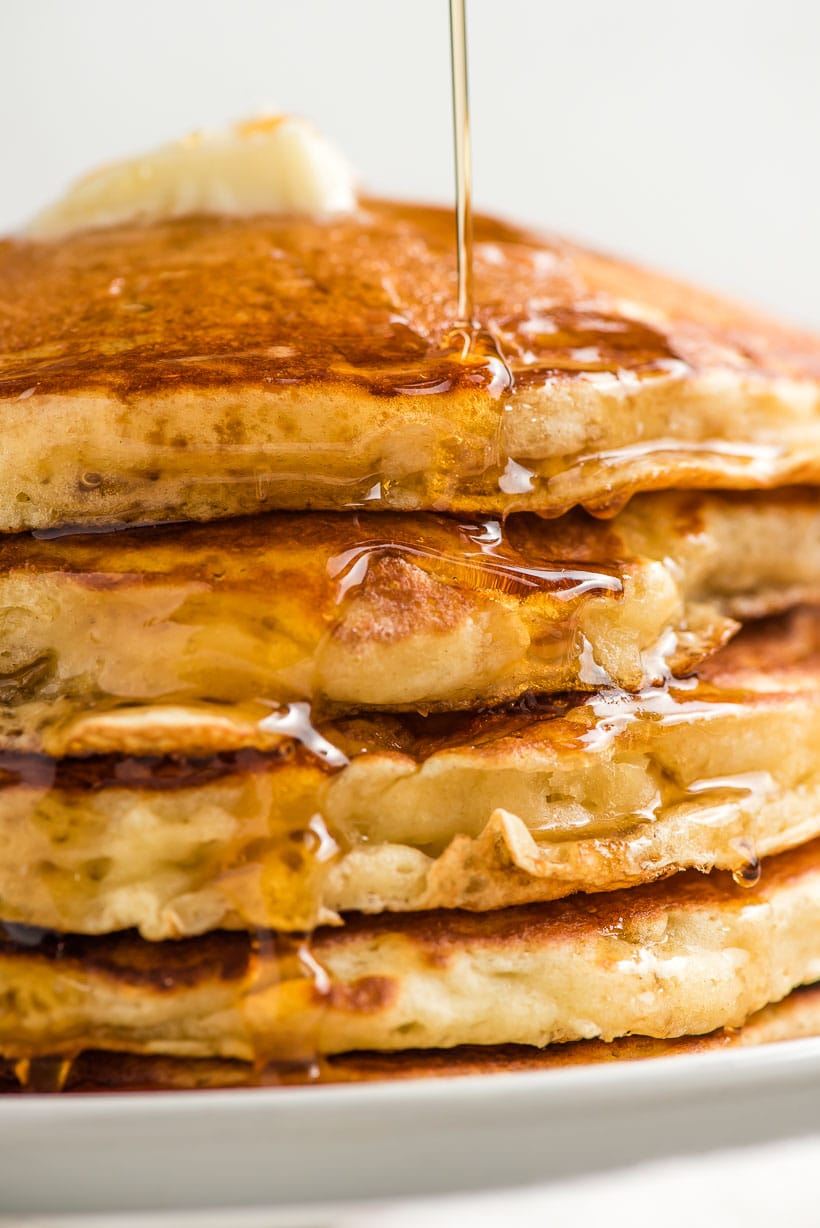 stream of syrup on a pile of fluffy pancakes