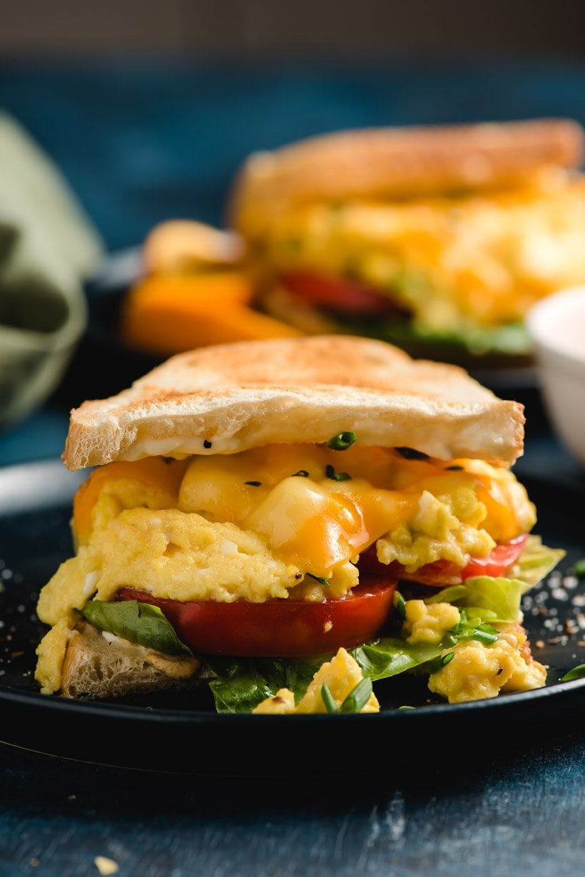 A scrambled egg sandwich seen from the side with layer of lettuce, tomato slices, scrambled eggs, cheese, and toasted bread.