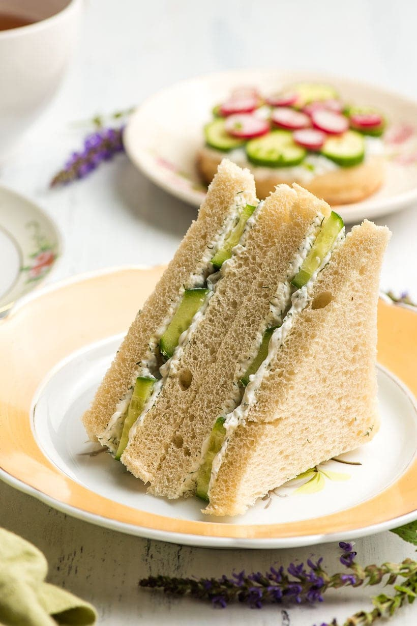 triangle cucumber sandwiches on a yellow rimmed plate