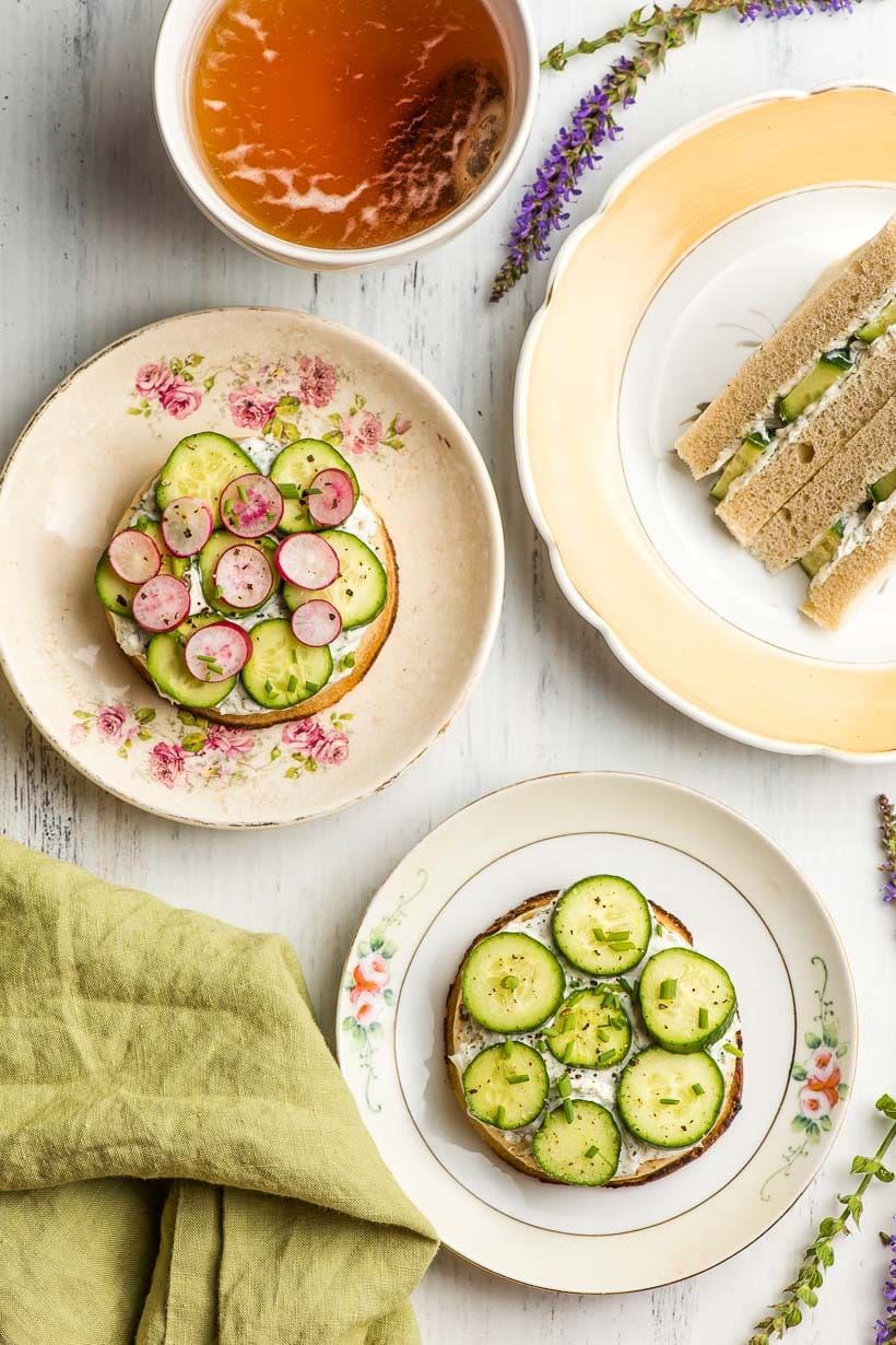 Multiple cucumber sandwiches on plates with a cup of tea