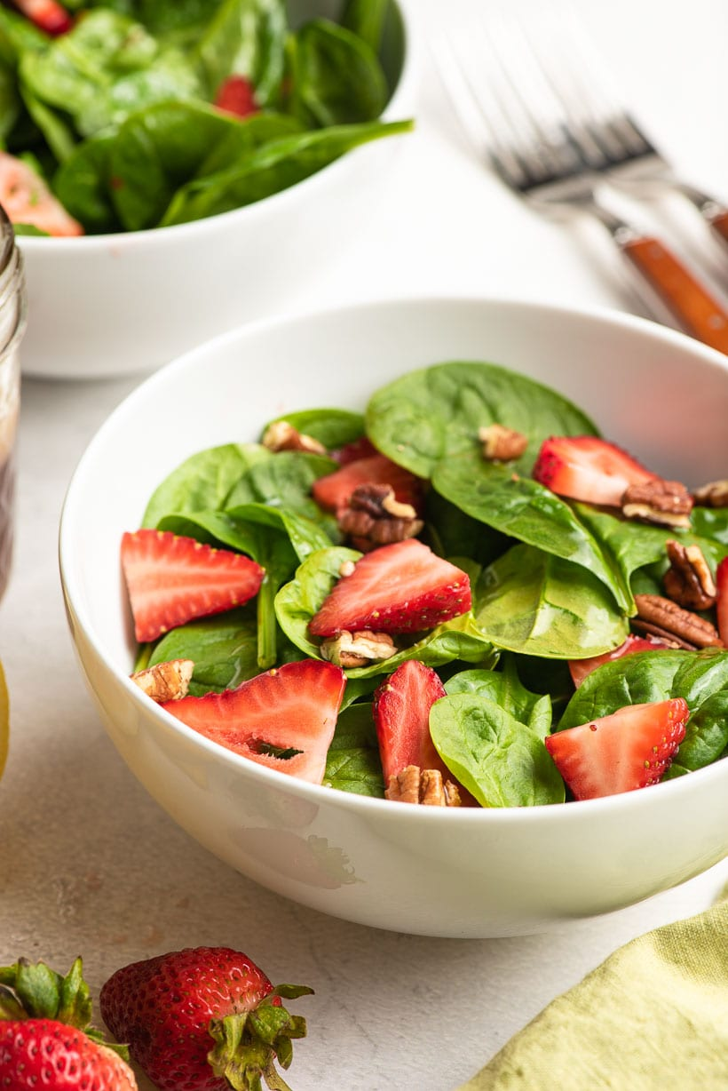 bowl of spinach salad with sliced strawberries and pecans