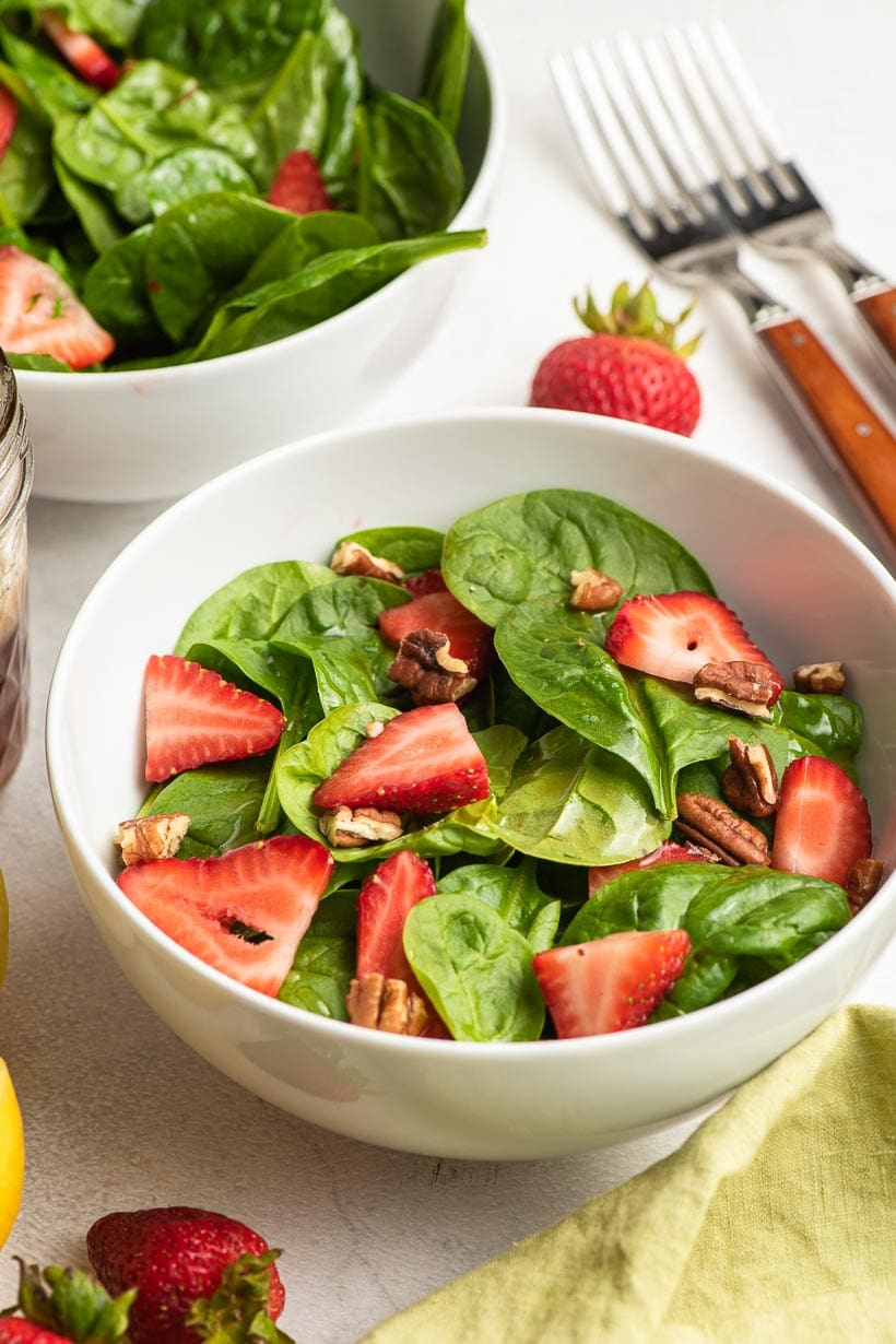 two white bowls with strawberry spinach salad