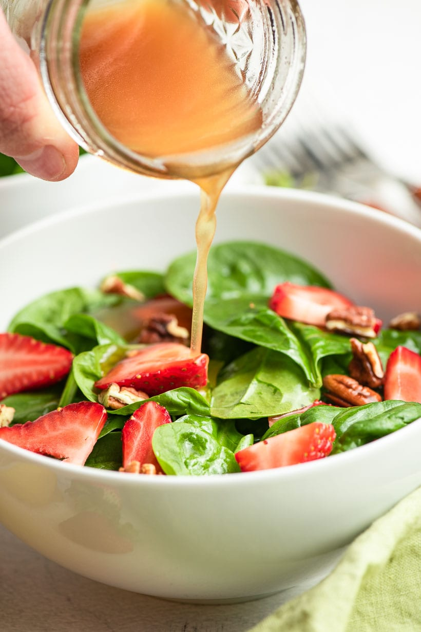 lemon dressing poured over a bowl of spinach salad