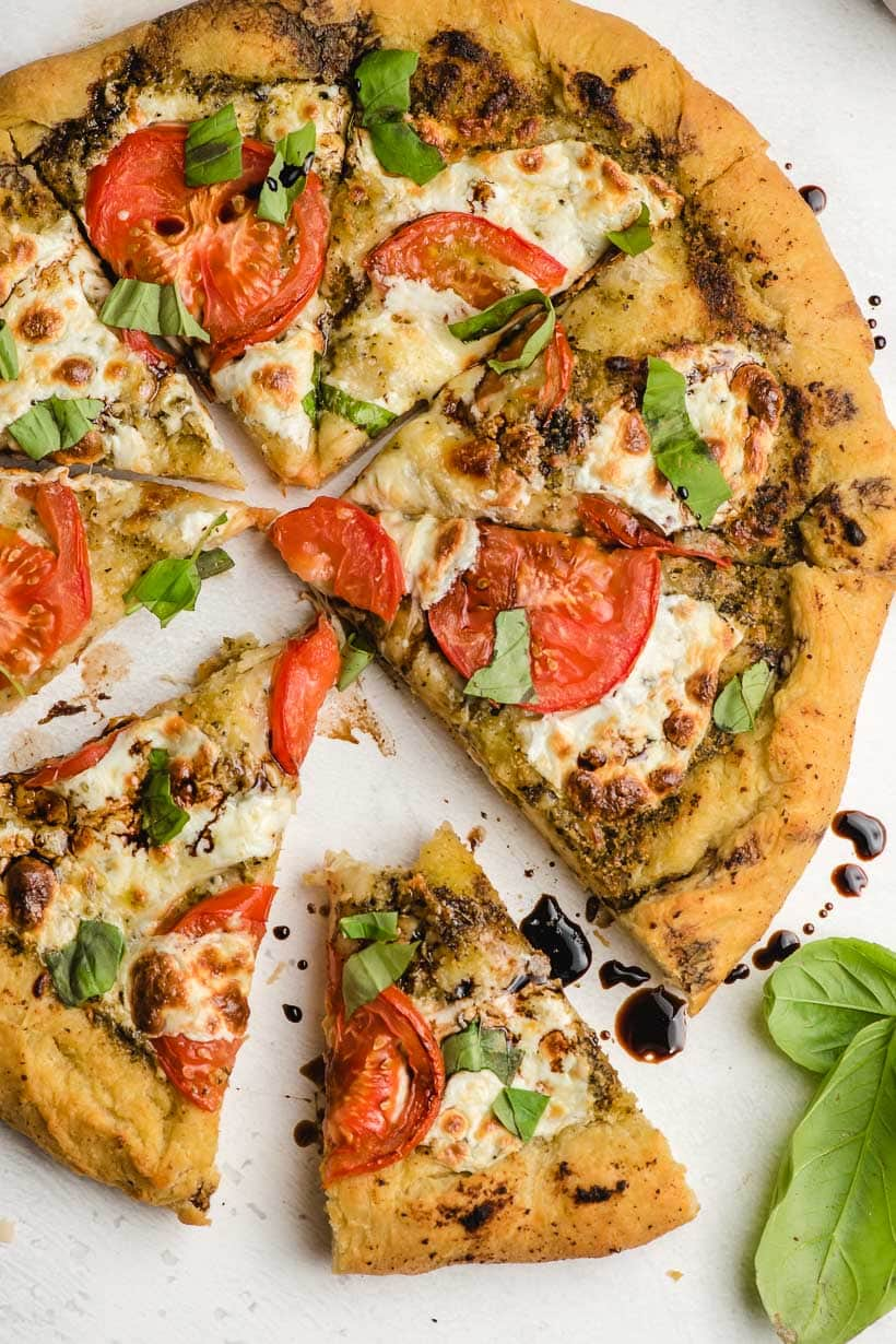 sliced caprese pizza with a bite taken out of one piece