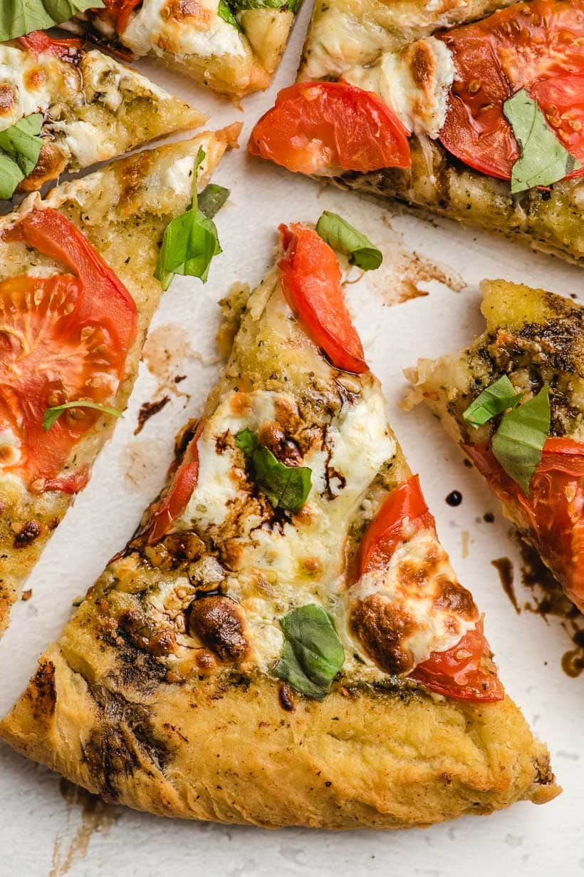 slice of caprese pizza with tomatoes and mozzarella