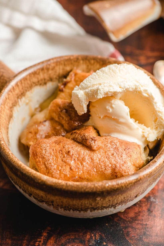 baked crescent roll apple dumpling with scoop of vanilla ice cream