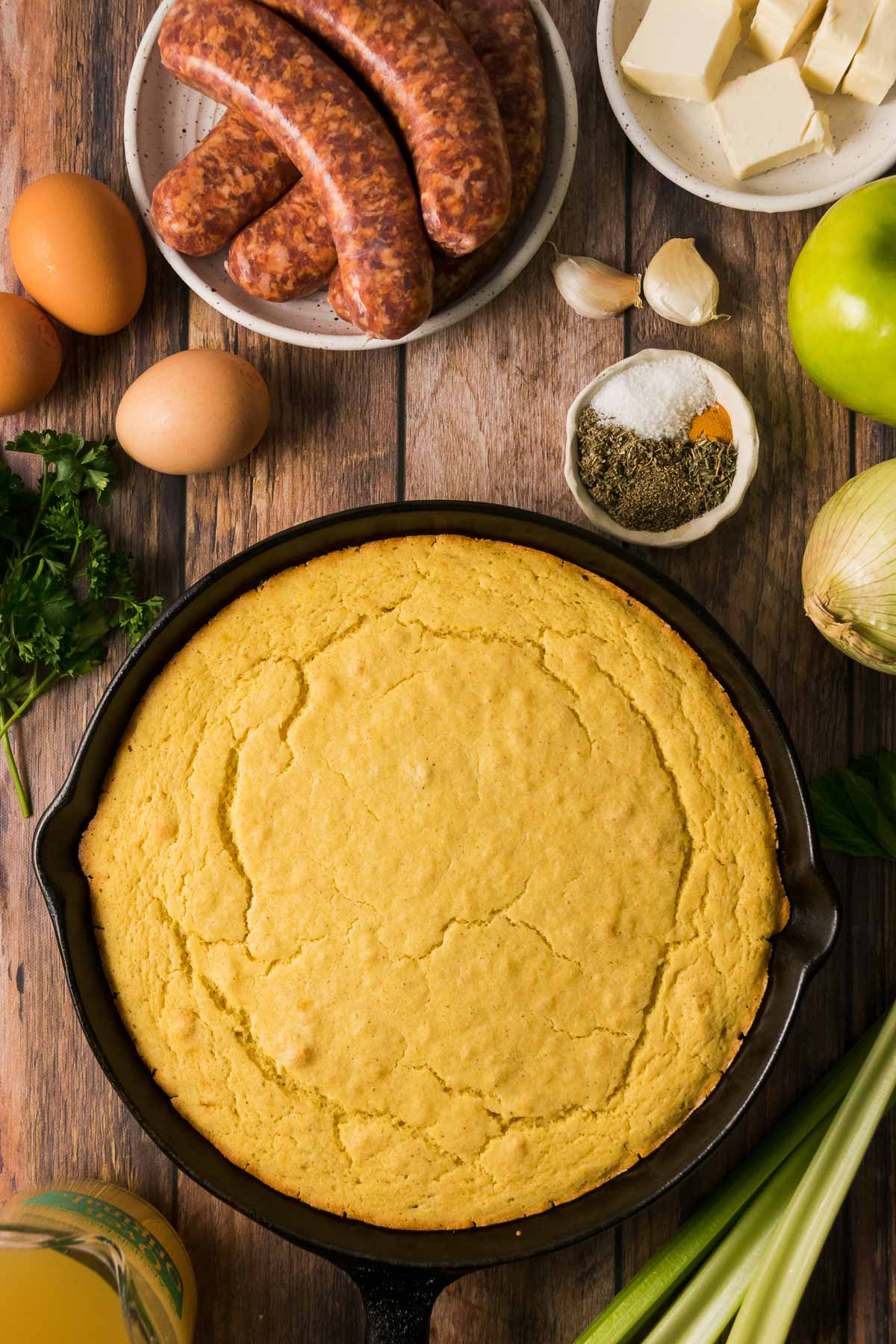 Cornbread in a cast iron skillet surrounded by bowls of seasonings, Italian sausage, eggs, apple, and butter.