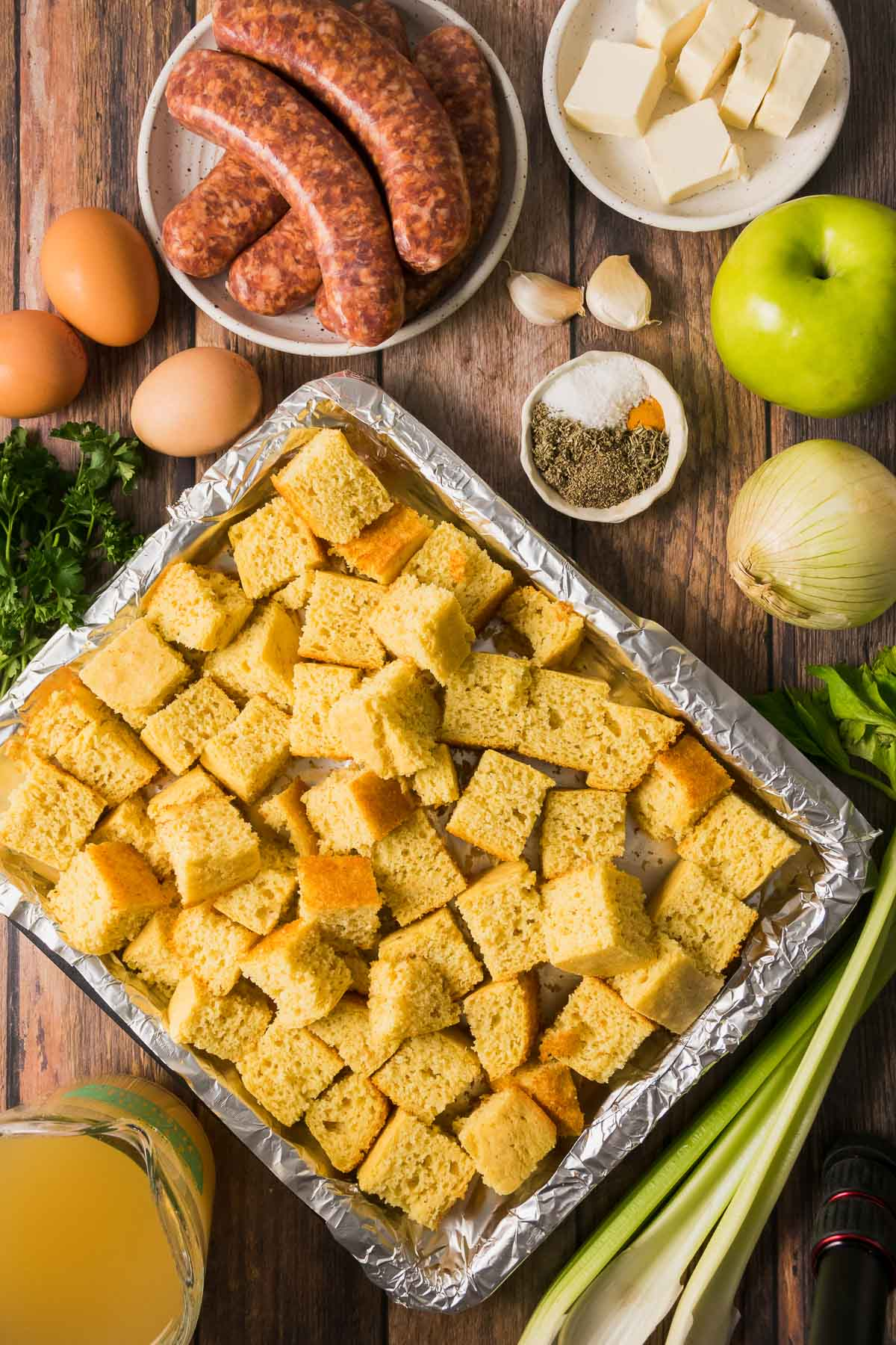 Ingredients for cornbread dressing- cornbread cubes, Italian sausage, eggs, a bowl of seasonings, garlic, butter, apple, onion, and chicken broth.