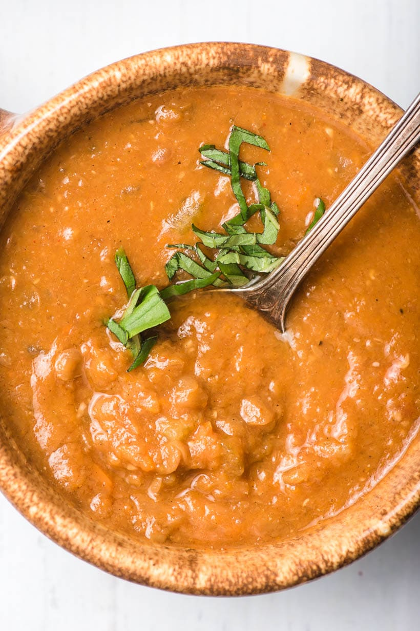 bowl of healthy lentil soup with basil and a spoon