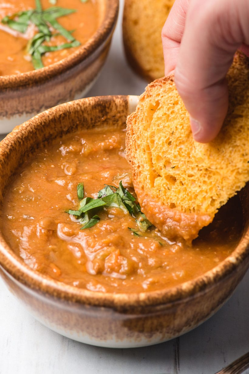bowl of vegan lentil soup with bread dipping into it