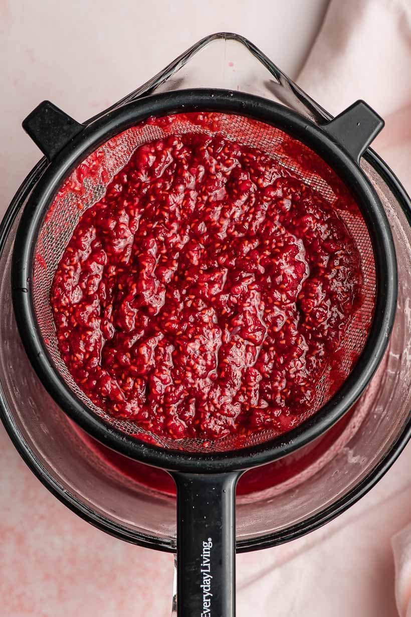 raspberry syrup being strained through a strainer