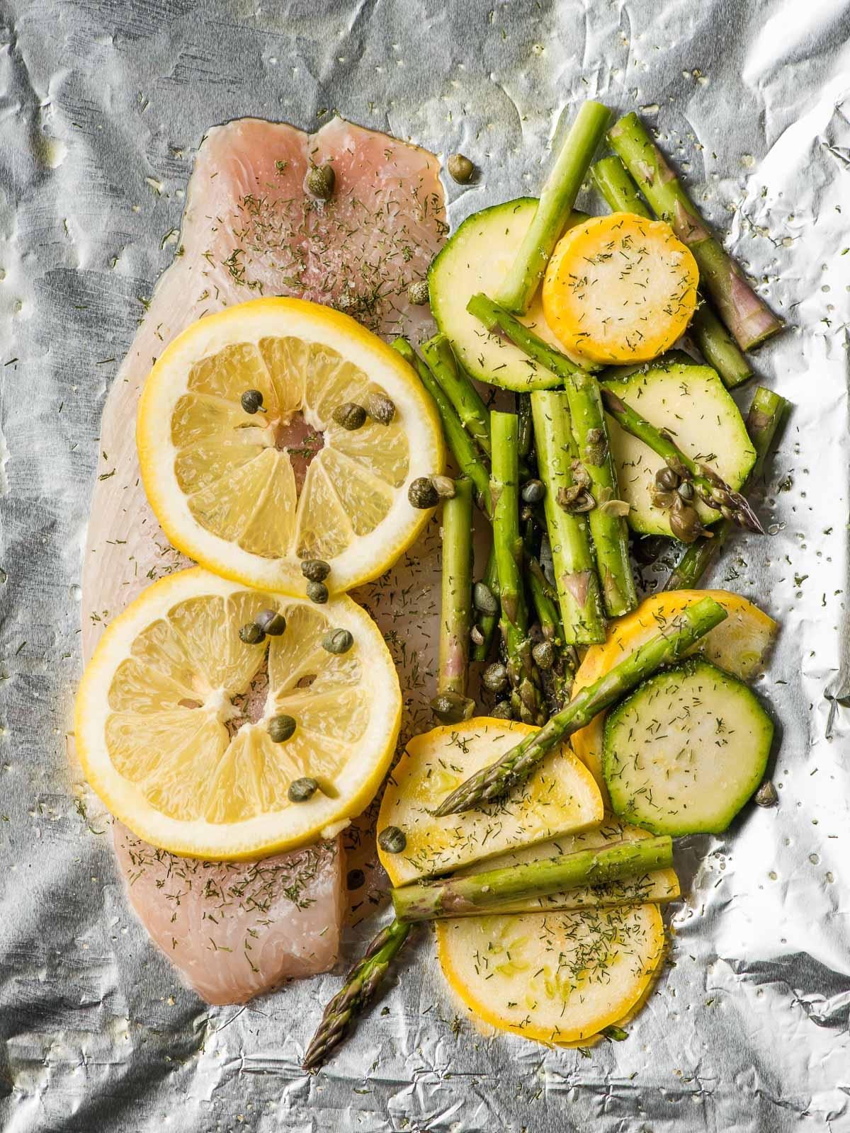 Foil packet loaded with uncooked tilapia fillet, sliced summer vegetables, slivers of butter, and lemon slices.