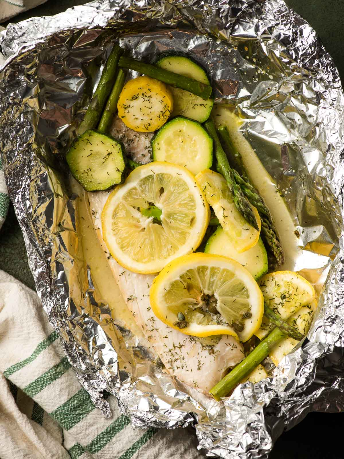 Tilapia fillet topped with lemon slices and surrounded by sliced squash and asparagus in a foil packet.