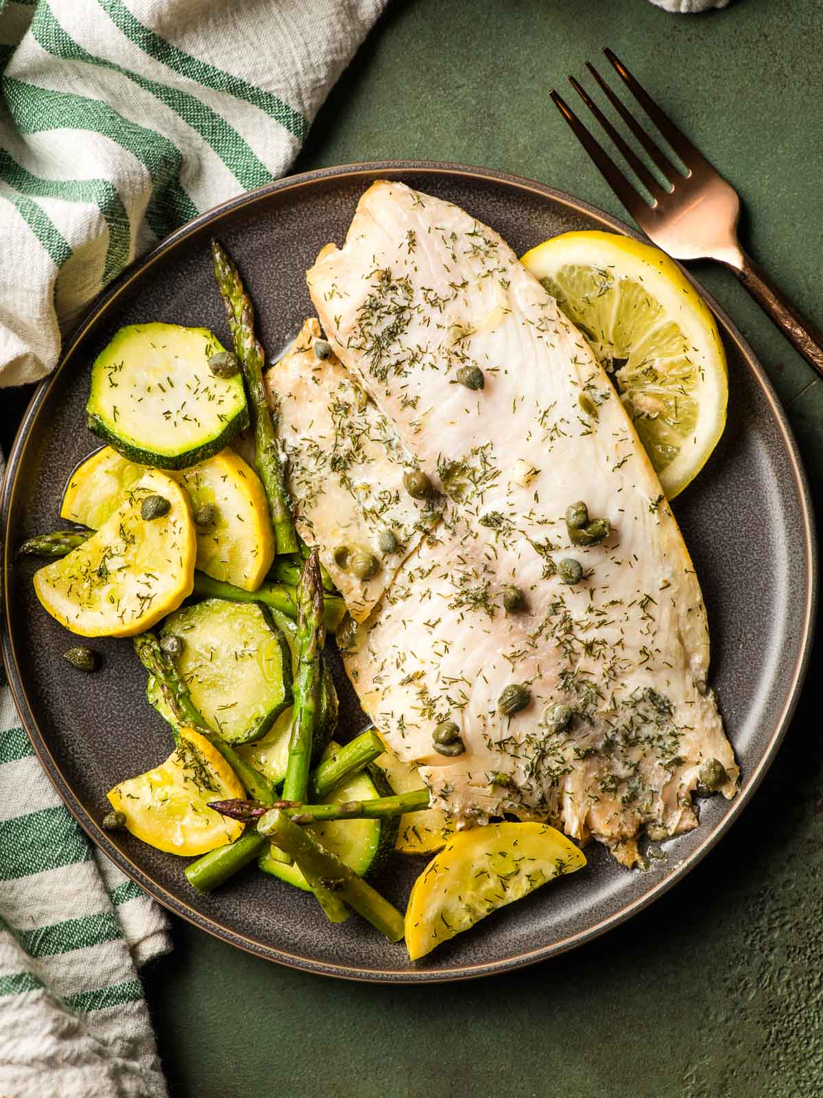 Dark gray plate with grilled tilapia fillet and summer veggies and lemon slice on the side.