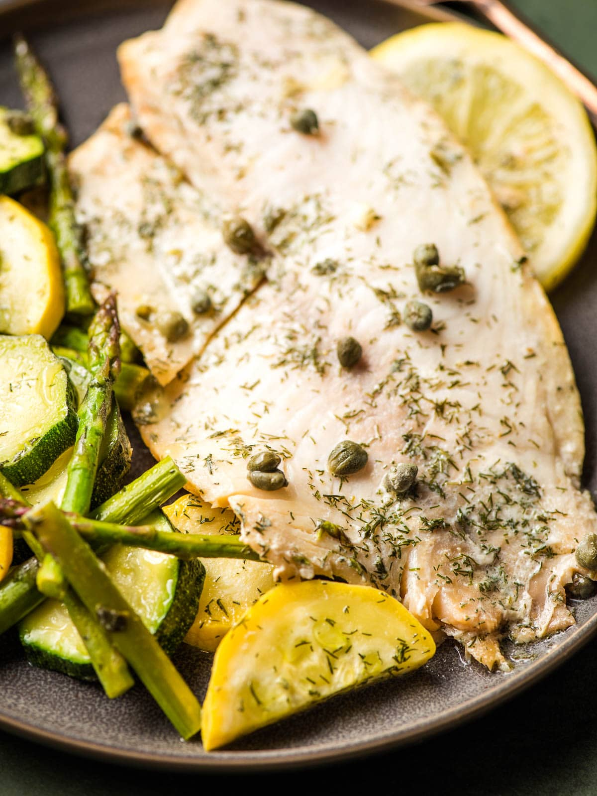 Seasoned tilapia fillet otpped with capers on a plate with sliced squash and asparagus.