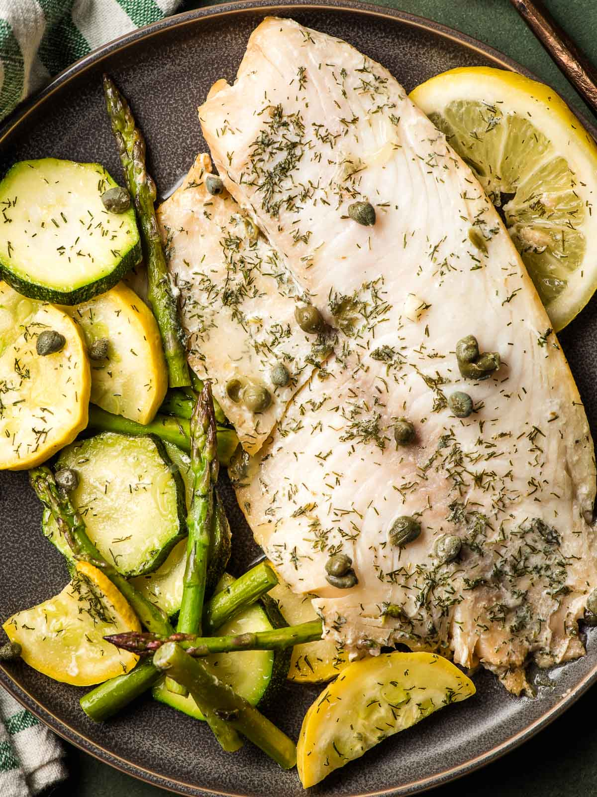 Grilled Tilapia topped with dried dill and capers on a palte with summer vegetables and lemon.