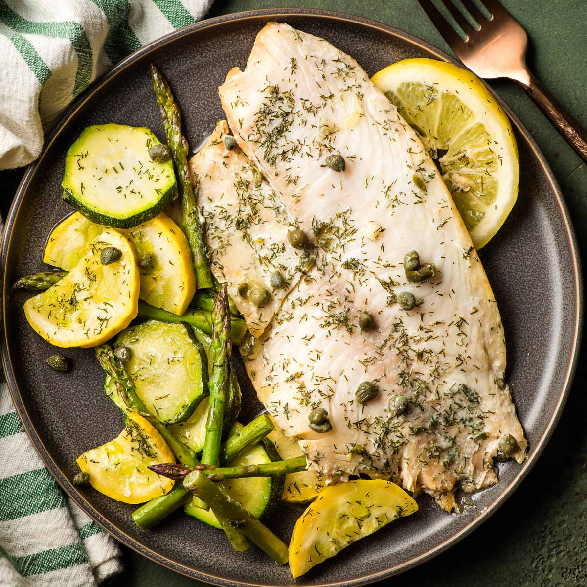 Grilled tilapia on a plate with sliced squash, zucchini, and asparagus.