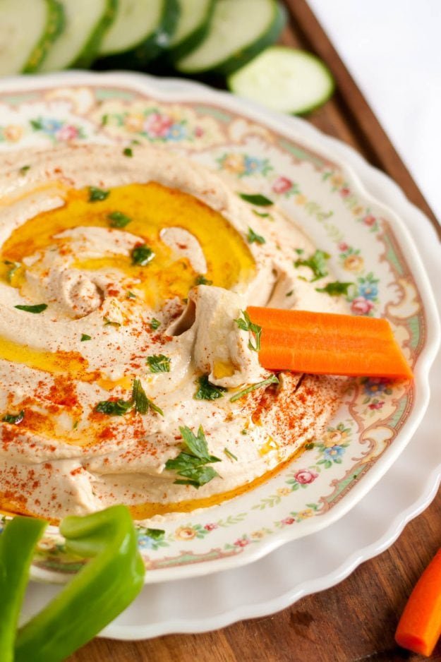 Image of carrot stick dipped in a bowl of Homemade Hummus