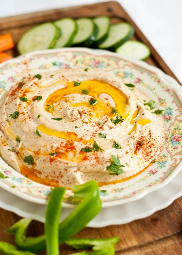 Image of a dish of Homemade Hummus surrounded by sliced veggies