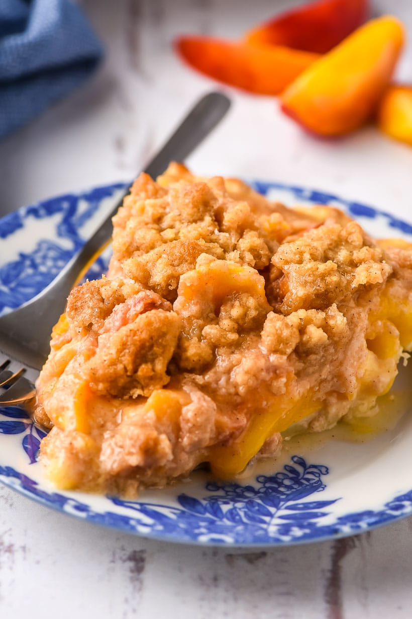 Slice of peach crumble pie on a white and blue plate