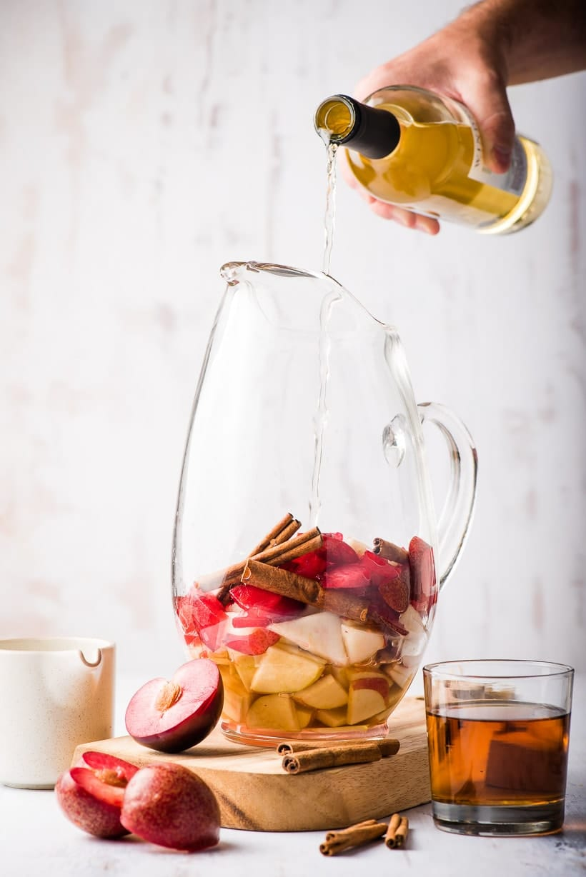 wine poured into pitcher of fall sangria