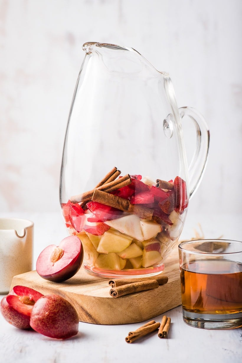 pitcher of autumn sangria with apples, plums, and pears