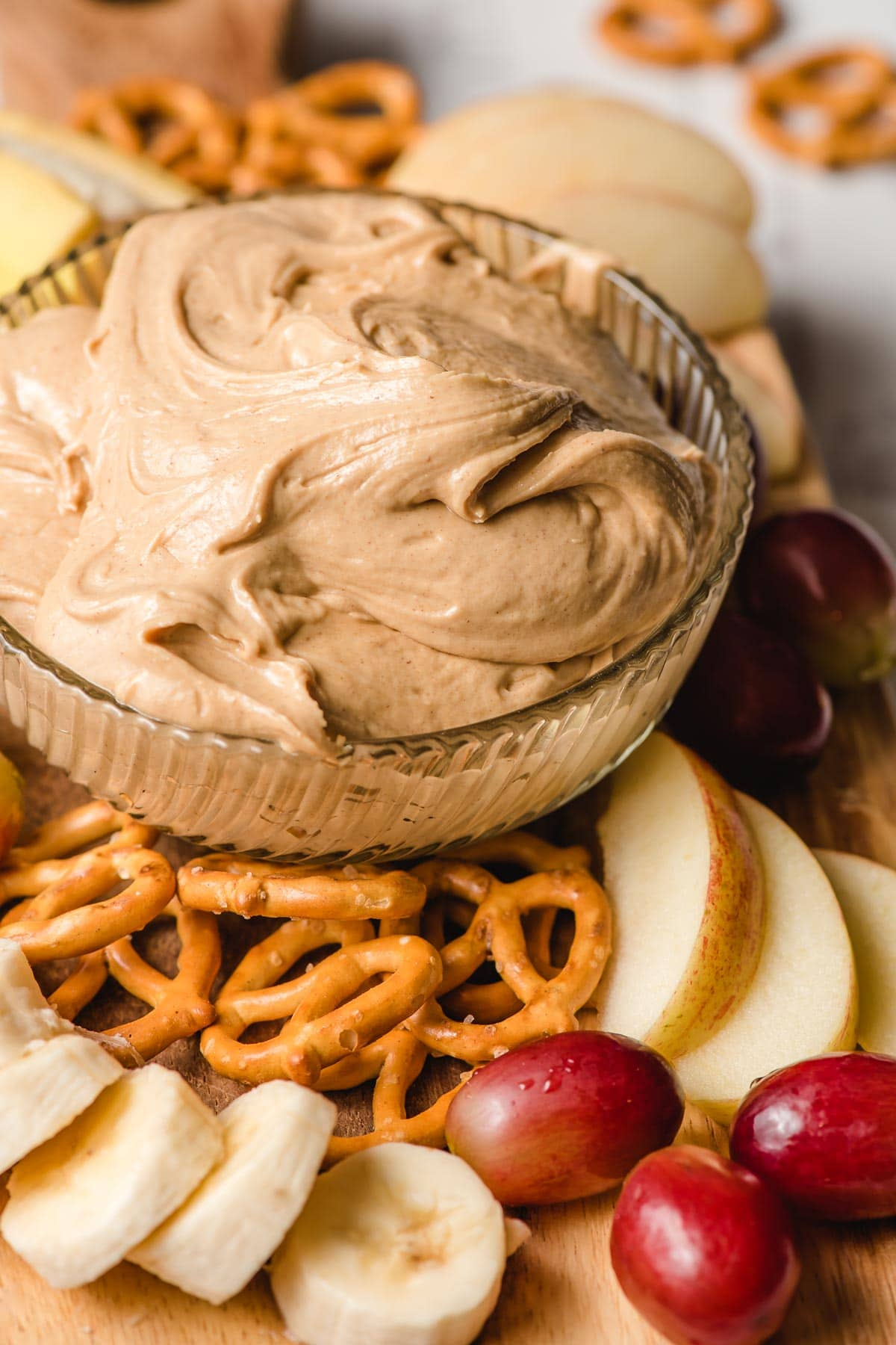 Amish church spread in a glass bowl surrounded by pretzels, apples, banana slices, and grapes.