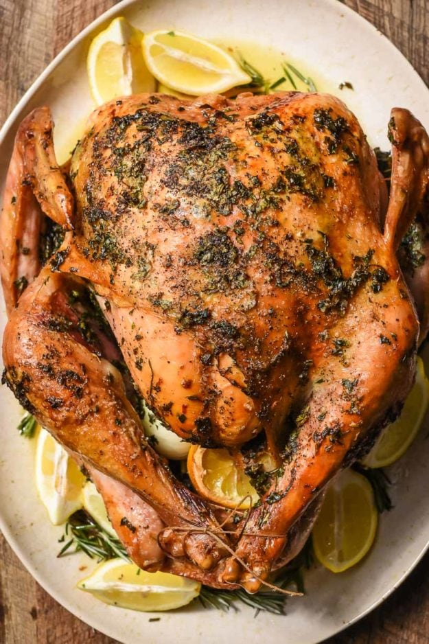 an oven roasted turkey served on a plate with herbs and lemon