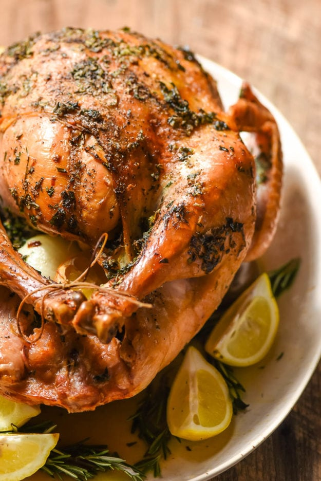 a golden brown oven roasted turkey sits on a serving platter
