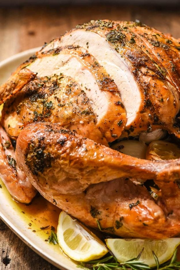 an oven roasted turkey partially carved on a serving platter with herbs and lemon