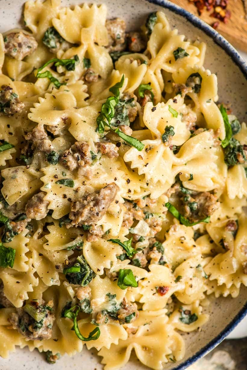 sausage and bowties in creamy sauce with kale