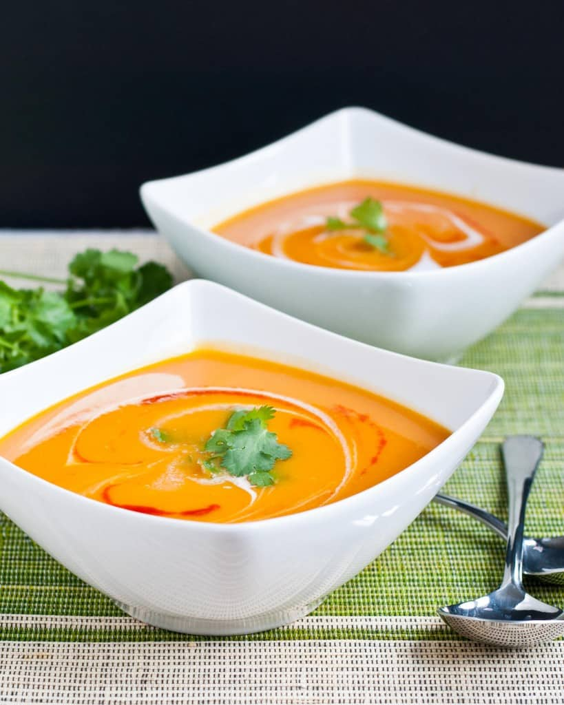 two white bowls filled with spicy sweet potato soup
