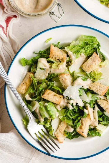 A blue rimmed white bowl holding a Caesar salad with croutons and shaved Parmesan.