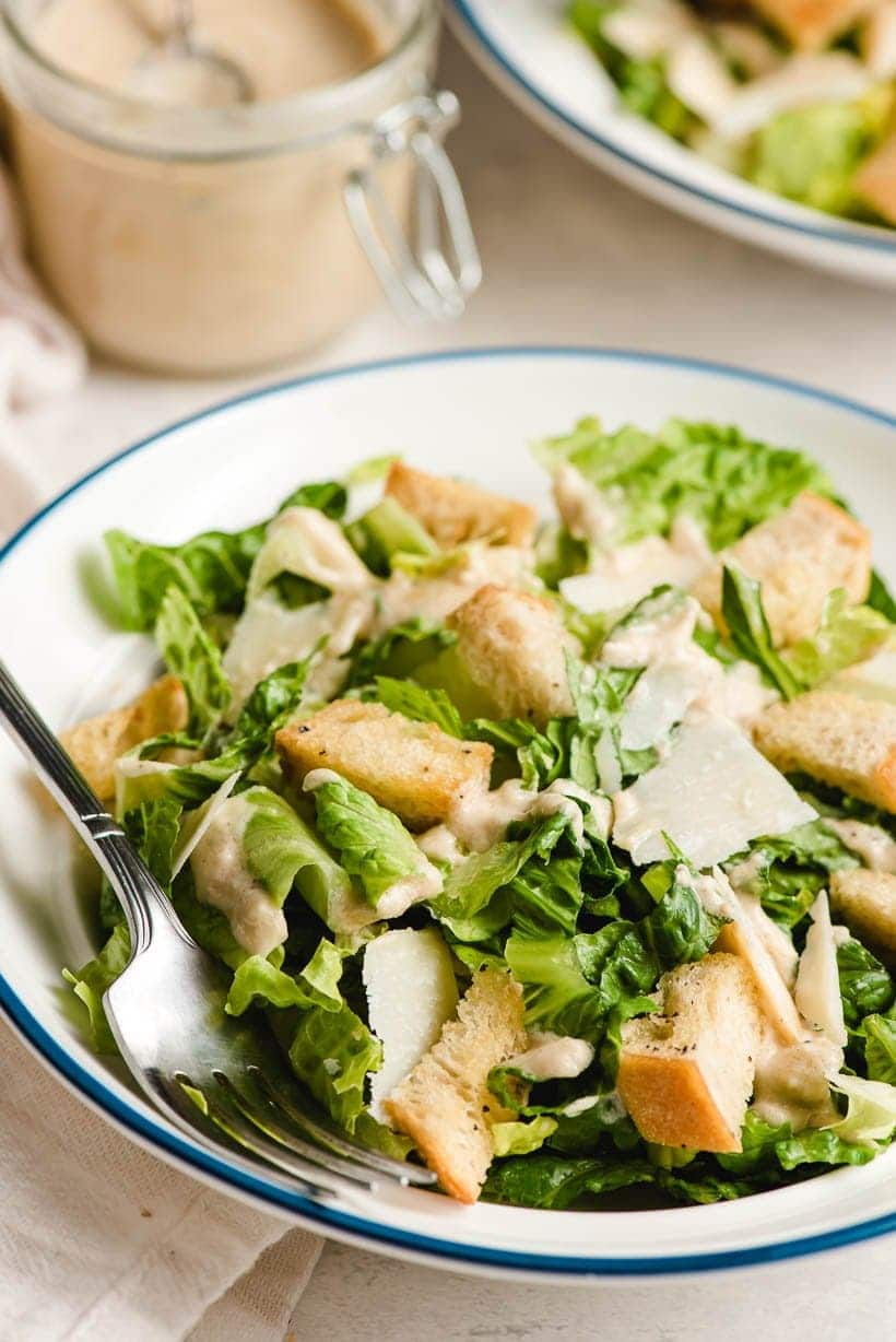 A white bowl filled with Caesar Salad , with a fork on the side.