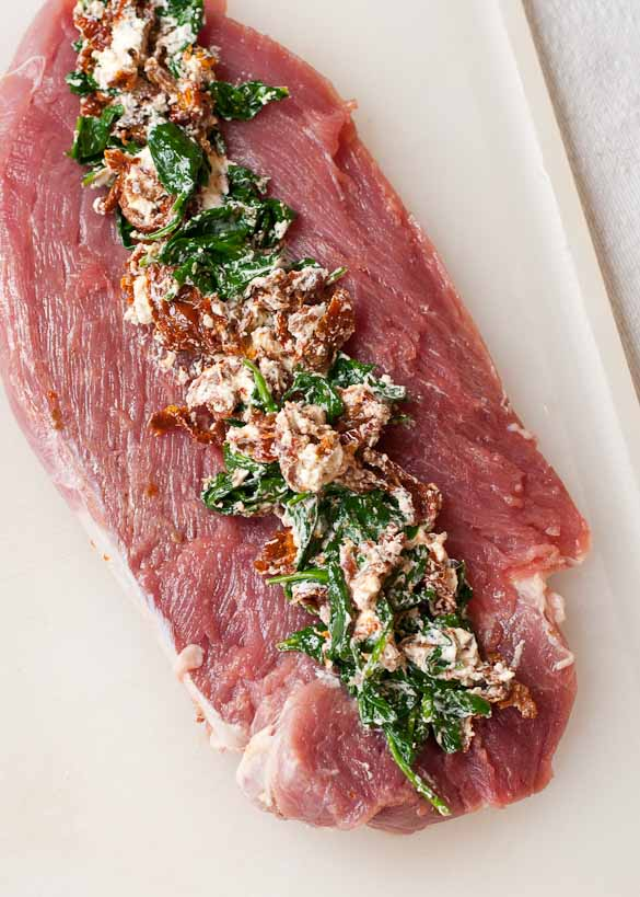 a raw pork tenderloin with mediterranean filling on a cutting board