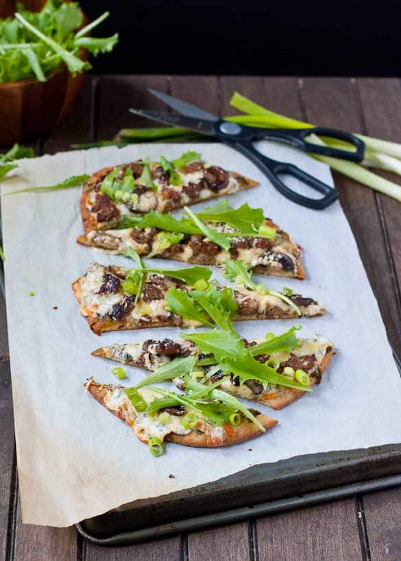 Fresh arugula gives this three cheese naan pizza a great peppery bite!